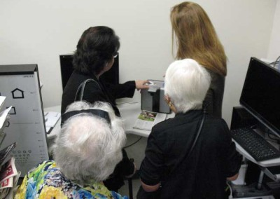 Administrative assistant Diane Wilkinson and members examining new style reading device